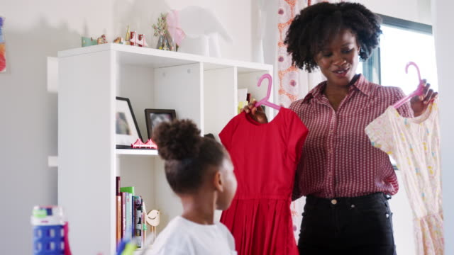 Mother helping daughter to choose outfit for school in bedroom at home - shot in slow motion