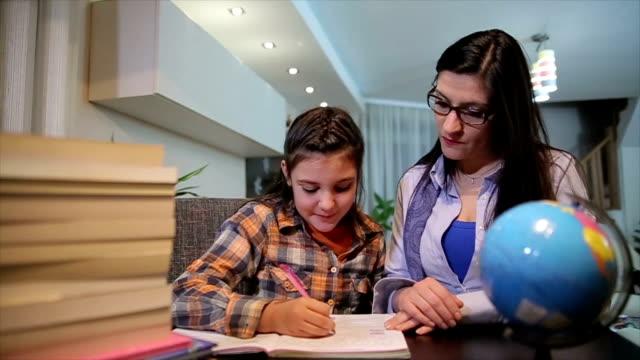 matka pomaga szczęśliwej córce w odrabianiu lekcji - praca domowa filmów i materiałów b-roll