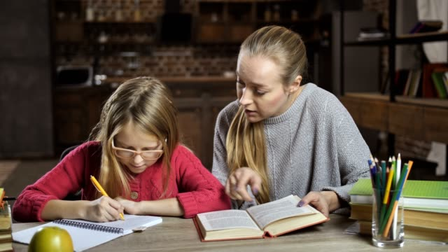 Mother helping her daughter with homework at home video