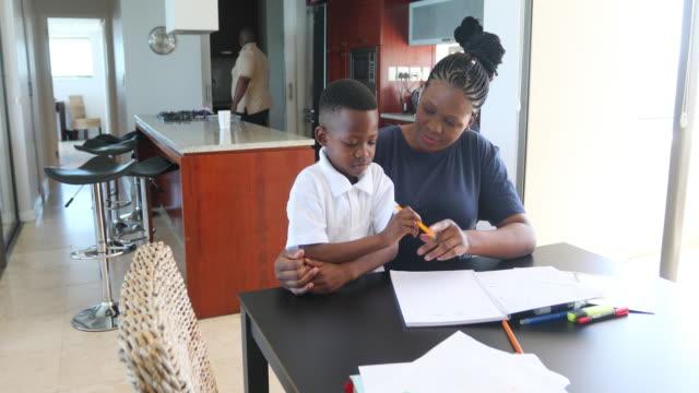 mother helping her son do homework at the dining room table - praca domowa filmów i materiałów b-roll