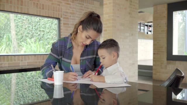 mutter hilft ihrem sohn bei hausaufgaben - lateinische schrift stock-videos und b-roll-filmmaterial