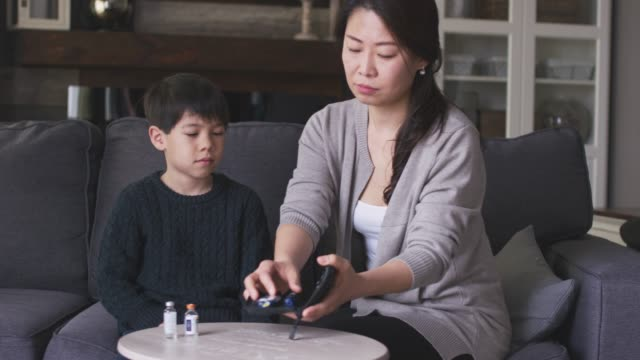 Mother helping son check blood sugar levels
