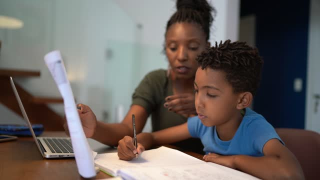 Mother helping son using laptop on homeschooling