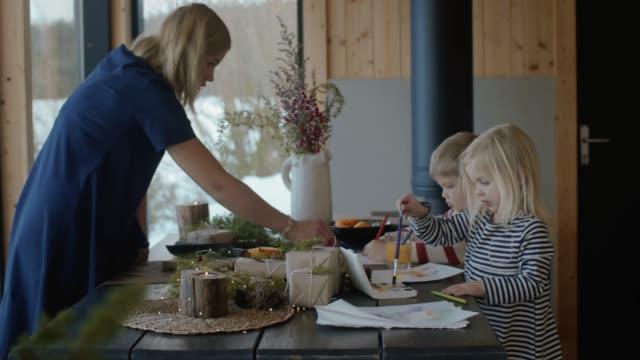 stockvideo's en b-roll-footage met moeder helpt kinderen om te schrijven een brief aan de kerstman (slow motion) - christmas cabin