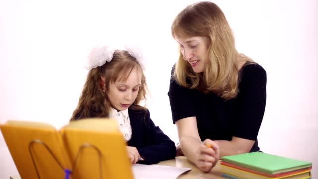 la madre aiuta la figlia a fare i compiti - nastro per capelli video stock e b–roll