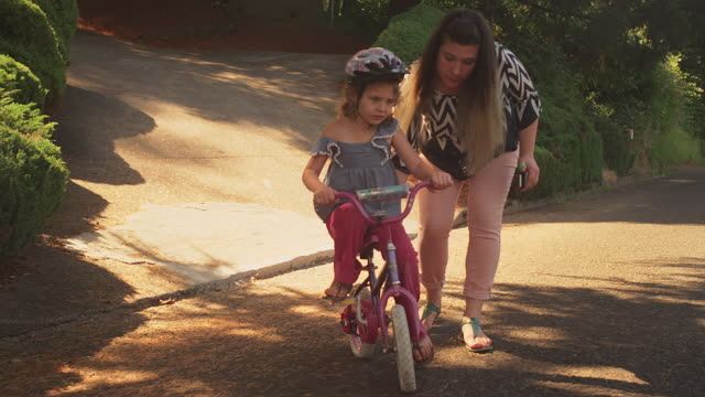 A mother helps her nervous daughter get started on her bicycle and the girl takes off video