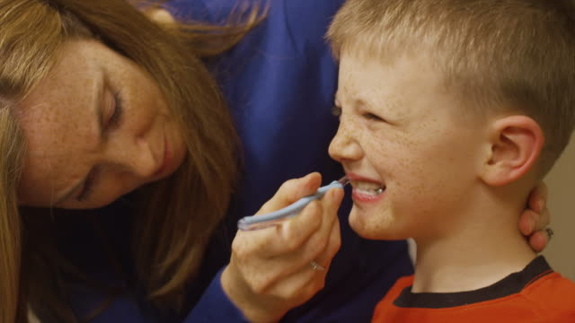 A mother helps her son brush his teeth video