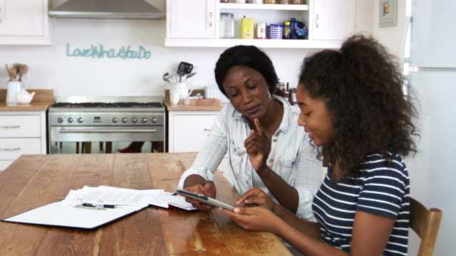 mother helps teenage daughter with homework using digital tablet - genitori video stock e b–roll