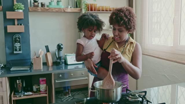 vídeos de stock, filmes e b-roll de mãe segurando filha de 3 anos e cozinhando macarrão - cozinha