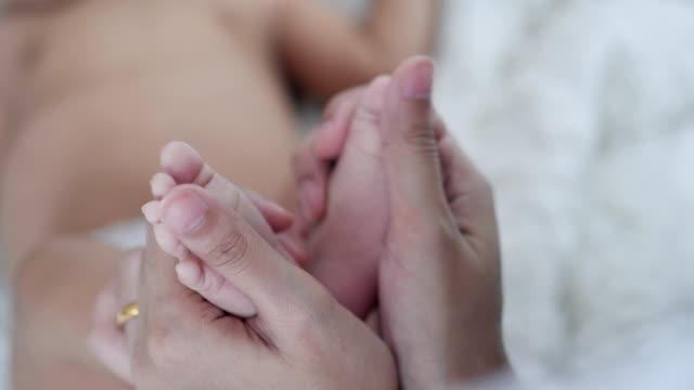 mother holding asian baby boy foot with love and kiss ,slow motion