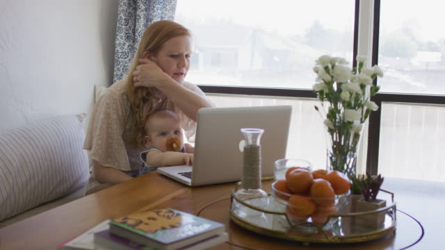 vidéos et rushes de tenue bébé de la mère comme elle fonctionne sur l'ordinateur - femmes actives