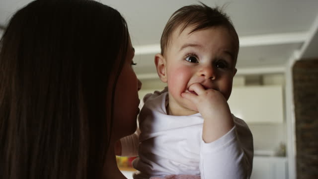Mother holding baby girl in her arms in living room video