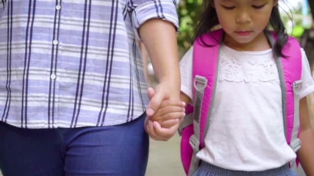 vidéos et rushes de mère retenant la main de la fille et marchant allant à l'école à l'extérieur. - élève