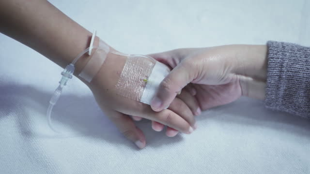 Mother holding hand of his son sick bed in the hospital. Touch the hand Slow motion. care encouragement