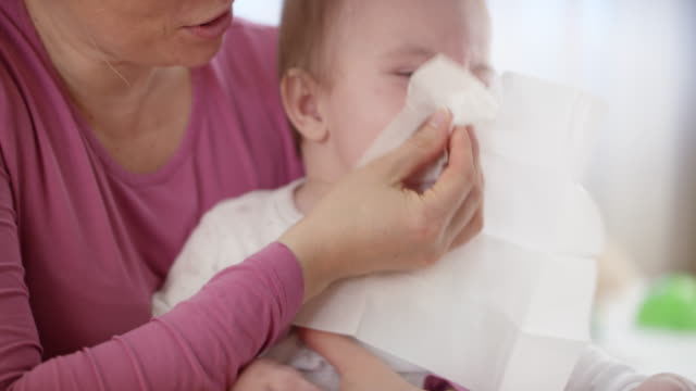 Mother holding her baby and wiping his nose video