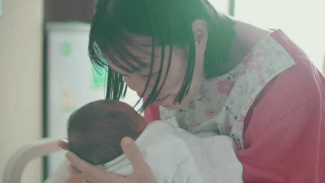 Mother Holding Newborn and Kissing
