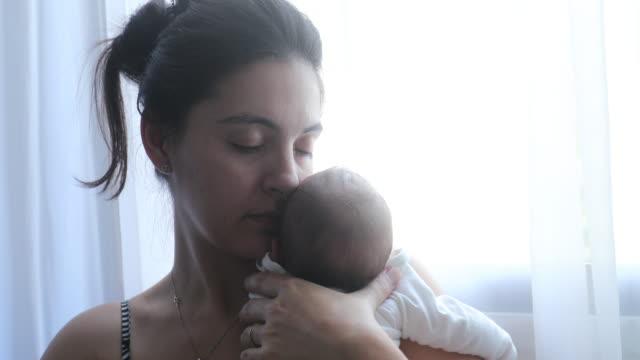 vídeos y material grabado en eventos de stock de madre sosteniendo al recién nacido junto a la ventana del hogar la primera semana de vida - nuevo bebé