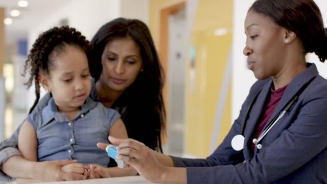vídeos de stock, filmes e b-roll de mãe que prende a filha nova em uma nomeação dos doutores - consciência negra