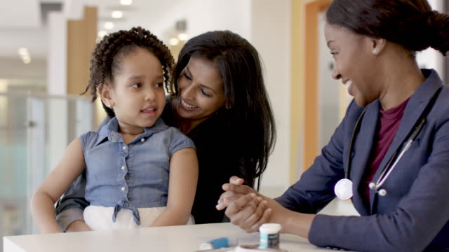 Mother Holding Young Daughter At A Doctors Appointment An ethnic mother is holding her young daughter at a medical clinic as an ethnic female doctor teaches them about diabetes and how to use an insulin pen. general practitioner stock videos & royalty-free footage