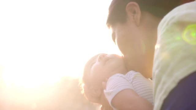 Mother Holds Baby In Arms and Kisses his Cheek video