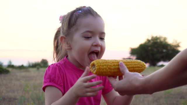 Mor rymmer majs till dottern i solnedgången video