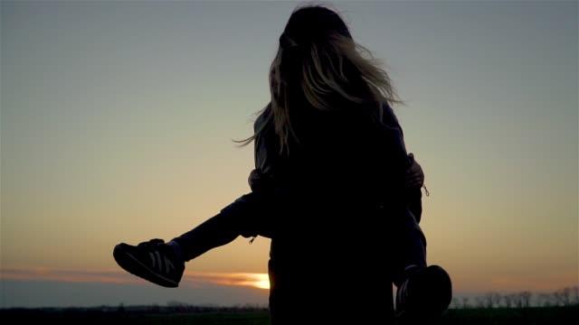 Mor håller sin dotter i armar och de snurrar och håret flyger på vind vid solnedgången i slow motion video