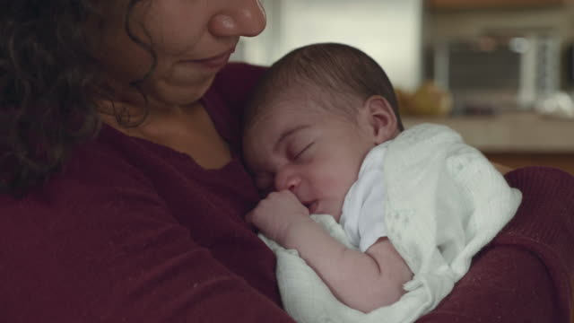 mother holds newborn infant in her arms - bambino appena nato video stock e b–roll