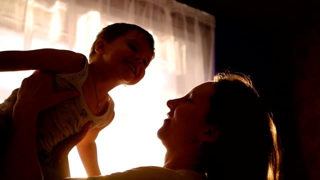 vidéos et rushes de mère tient le fils à la maison par le soleil. s'amuser rire papa en slowmotion ludique - 0 11 mois