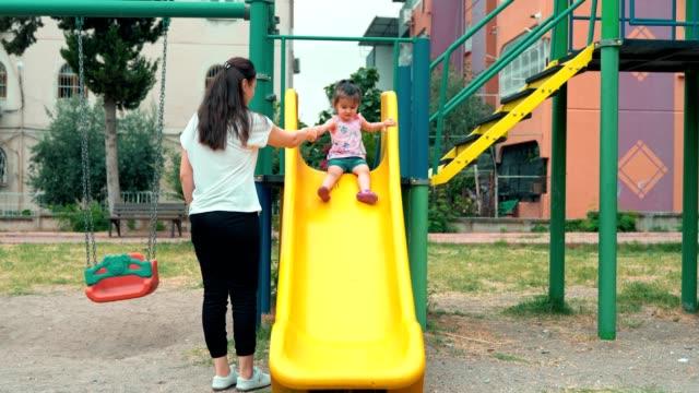 vidéos et rushes de une mère tient les mains d'une jeune fille glissant vers le bas d'un toboggan dans le terrain de jeu à l'extérieur. une petite fille apprend à monter un toboggan par une chaude journée d'été. - glisser