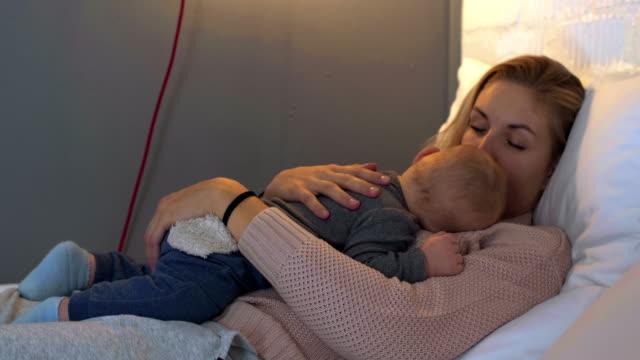mamma kramar hennes sovande barn - baby sleeping bildbanksvideor och videomaterial från bakom kulisserna