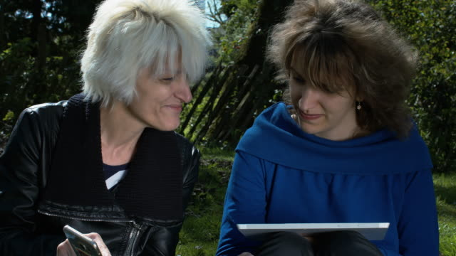 A Mother In A Skin Coat And Her Daughter, Dressed In Blue Enjoying A Spring Day In The Park video