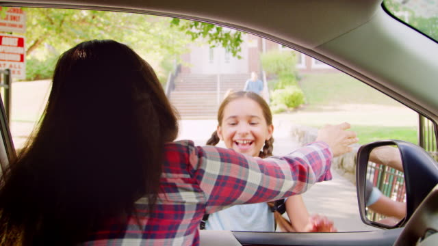 mother in car collecting daughter in front of school gates - podnosić filmów i materiałów b-roll