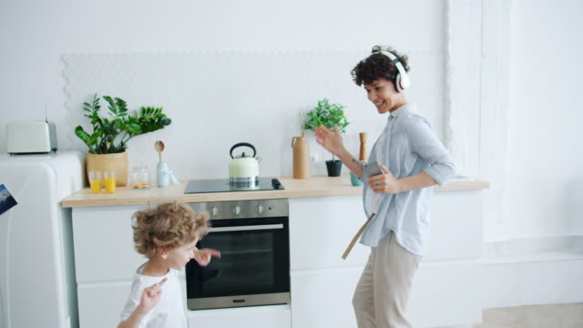Mother in headphones and small son dancing in kitchen having fun together