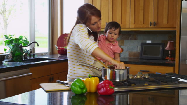 Mother in kitchen with young daughter video