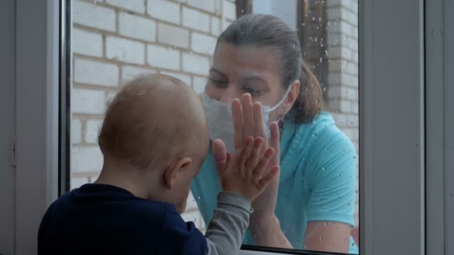 mother in mask and her baby communicate through glass of door during quarantine - hand on glass covid video stock e b–roll
