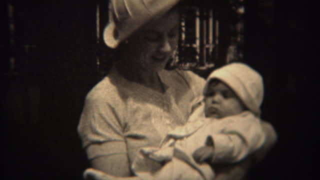 1937: Mother in white fashion hat holding baby daughter in matching outfit. video