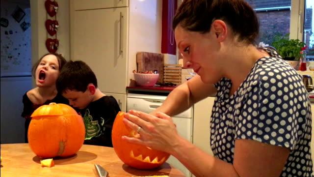 母は、ハロウィーンの仮装衣装で彼女の子供の腕時計としてカボチャを彫り、 - 彫刻点の映像素材/bロール