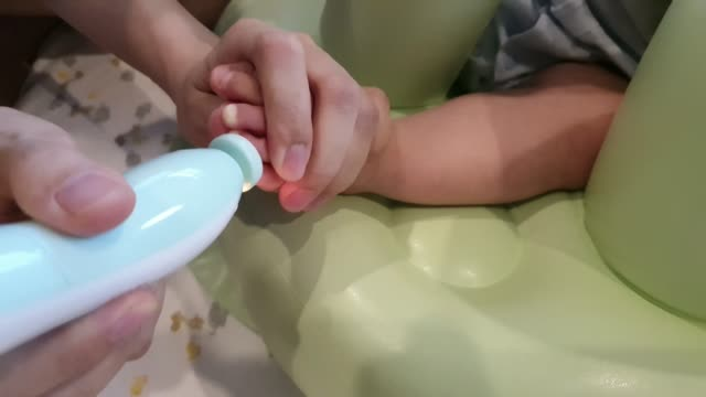Mother is filling baby toe nails, difficult holding foot by her hand,using automatic file machine while baby movement is very convinience and easily triming by let's your baby take a seat.