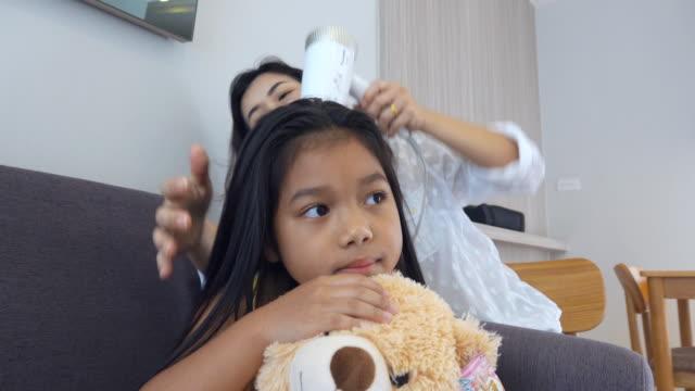 vidéos et rushes de la mère sèche ses cheveux de fille après un bain dans le salon - salons et coiffeurs