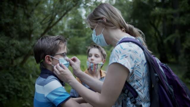 anne covid-19 salgını sırasında parkta maskeleri ayarlamak için çocuklara yardımcı oluyor - ayarlamak stok videoları ve detay görüntü çekimi