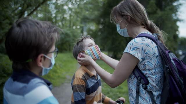 vidéos et rushes de une mère aide les enfants à ajuster les masques dans le parc pendant la pandémie de covid-19 - enfant masque