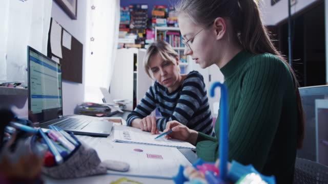 vídeos de stock, filmes e b-roll de mamãe está ajudando a filha com lição de casa no quarto. - adolescência