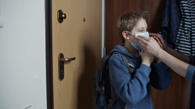 媽媽正在幫助兒子戴上面罩 - back to school 個影片檔及 b 捲影像