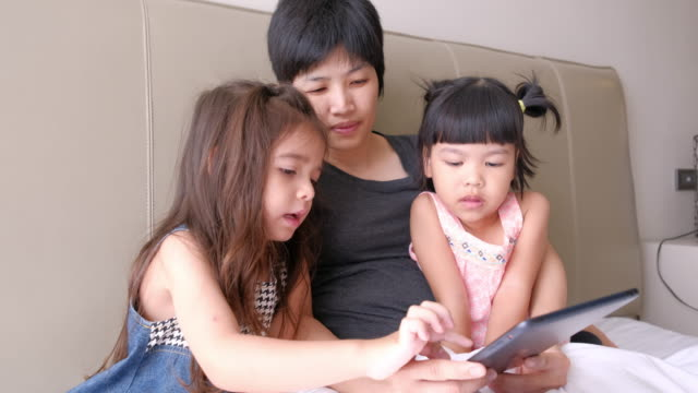 Mother is playing digital tablet with her daughter video