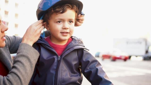 vídeos de stock e filmes b-roll de mother is putting safety helmet on his little son's head - proteção