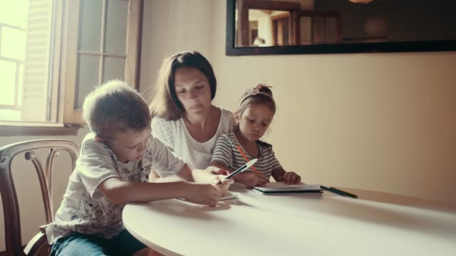 mother is spending time with children drawing (slow motion) - ręczna kamera filmów i materiałów b-roll