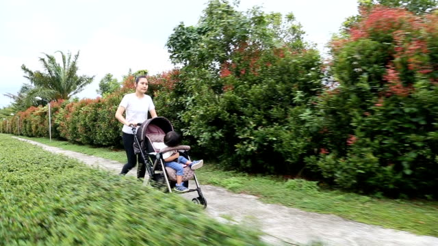 Mother jogging with baby boy in stroller. video