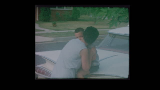 1964 mother kisses son goodbye and little boy gets on antique school bus - kids kiss embarrassed video stock e b–roll