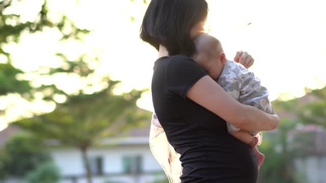 Mother kissing her son in the park