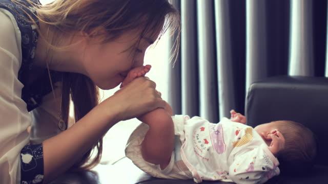 Madre poco besando bebés pies - vídeo